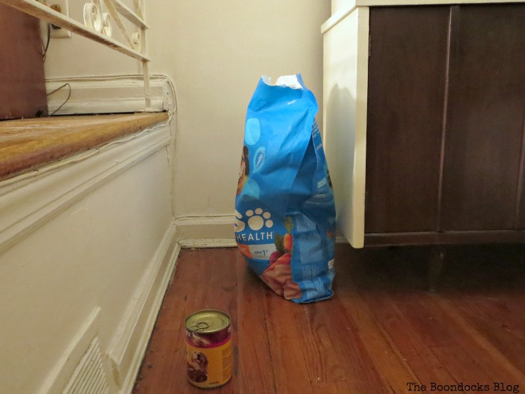 Bag of dog food and can in corner of dining room.