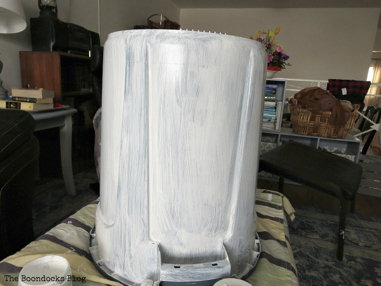 Painting bottom of bucket with white paint.