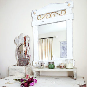Painted white wood mirror over a white painted dresser.