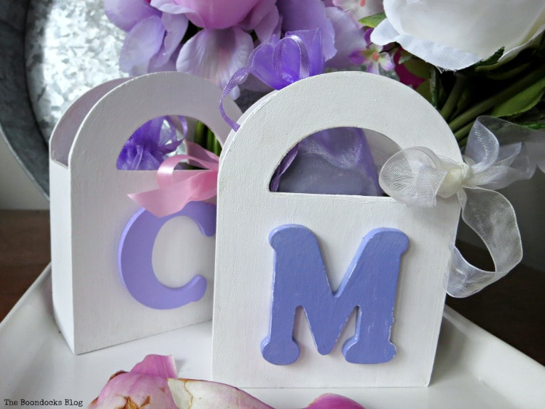 Two white painted wooden gift bags with letters and ribbons, with bars of soap inside and bouquets of faux flowers, Gift Giving with Pretty Wooden Gift Bags www.theboondocksblog.com