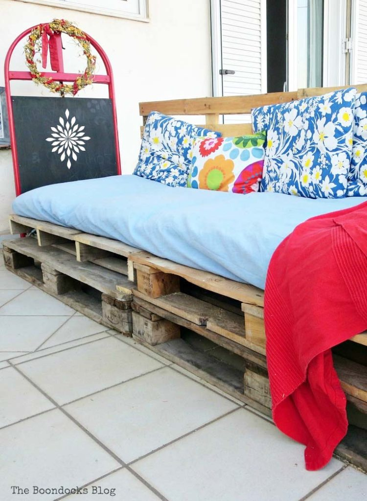 A completed DIY pallet couch covered with colorful cushions and blankets.