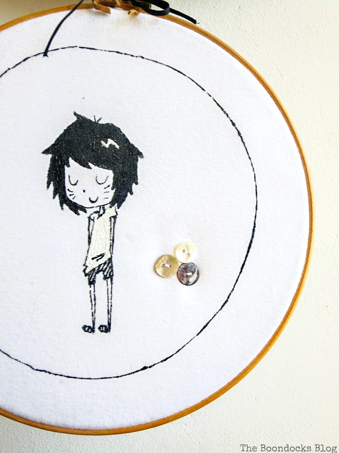 Close up of hoop wall art made from an upcycled tshirt. It shows a girl character and three sewn on buttons.