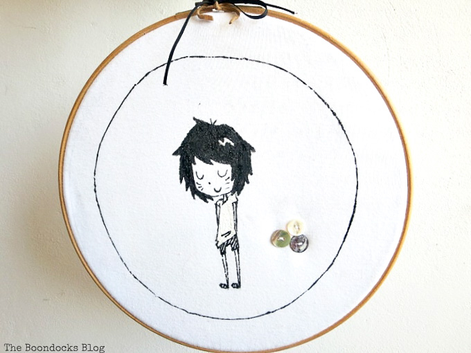 upcycled tshirt placed into the embroidery hoop and hung on the wall.