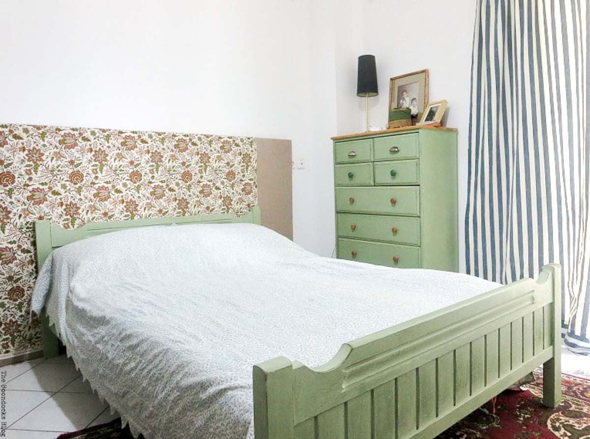 Green painted dresser and bed frame. The bed has a flower fabric head board.